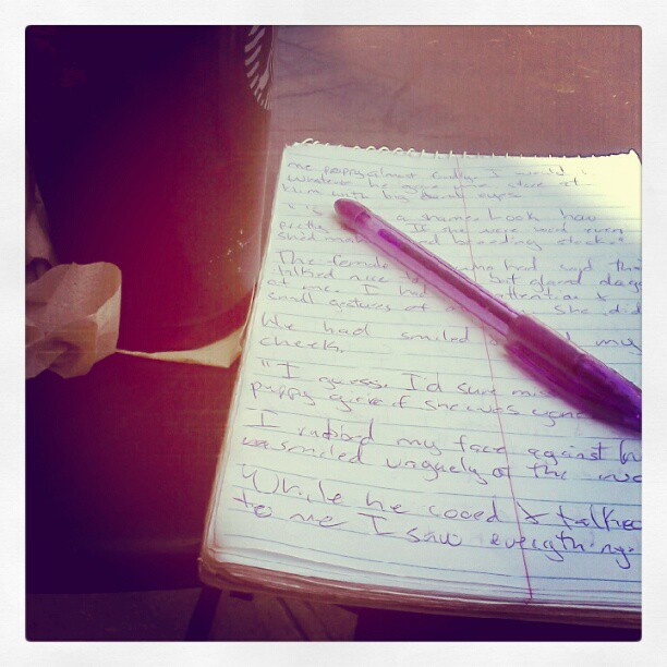 Picture of a giant cup of coffee on the left and a notepad and purple ink pen on the right.